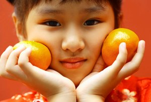 getty_rf_photo_of_young_asian_girl_with_oranges